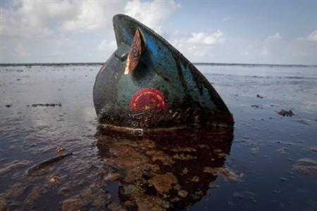 A hard hat from an oil worker lies in oil from the Deepwater Horizon oil spill on East Grand Terre Island, Louisiana in this June 8, 2010 file photo. REUTERS/Lee Celano/Files