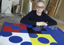 <p>Swiss-French artist Francis Baudevin poses in front of the poster he designed for the upcoming Montreux Jazz Festival during a presentation in Lausanne November 26, 2010. REUTERS/Denis Balibouse</p>