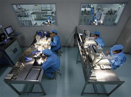 Employees work at a LED panel production line in a factory in Suining, Sichuan province, China, November 11, 2010. REUTERS/Stringer