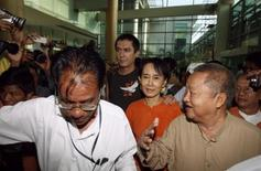 <p>Myanmar's pro-democracy leader Aung San Suu Kyi (C) makes her way with her son Kim Aris (2nd L) through the airport building as he leaves Yangon December 7, 2010. REUTERS/Soe Zeya Tun</p>