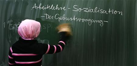 A pupil wipes a blackboard in a German basic primary school in Berlin November 3, REUTERS/Tobias Schwarz