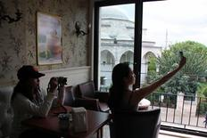 <p>Traveler Sumin Kim, 29, of Ilsan, Korea, (L) looking at her camera while traveling companion Sul-hee Kim, 25, of Seoul, (R) looks for Wi-Fi on her iPhone 4G in a restaurant in the Sultanhamet area of Istanbul, Turkey on September 30, 2010. REUTERS/Natalie Armstrong</p>