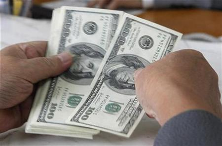 A customer counts U.S. dollar notes at a bank in Hanoi November 29, 2010. REUTERS/Kham