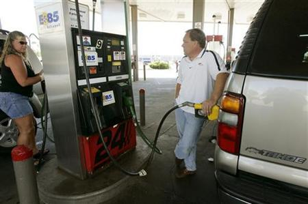 A man fills his 2002 Chevrolet Tahoe with E85 fuel, a blend of 85% denatured ethanol and gasoline at a gas station in Greeley, Colorado July 7, 2006. REUTERS/Rick Wilking