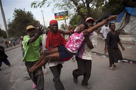 A woman overwhelmed by teargas released by U.N. troops is carried to a Red Cross clinic in Port-au-Prince as protesters clashed with troops in the wake of yesterday's release of preliminary election results for Haiti's countrywide elections December 8, 2010. REUTERS/Allison Shelley