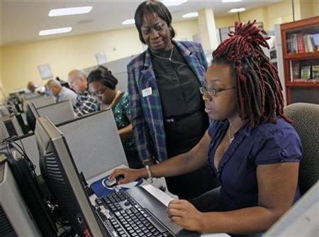 Shaneika Smith (R) of West Palm Beach, FL, fills out an online job application with the help of career consultant Verdina Coleman (C) at the Workforce Alliance Career Center in West Palm Beach, Florida December 2, 2010. REUTERS/Joe Skipper