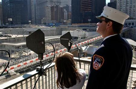 A firefighter stands with daughter during fourth anniversary of attacks on the World Trade Center in New York. REUTERS/Chip East
