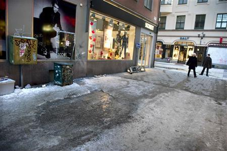 People pass a bomb blast site in central Stockhom December 12, 2010. REUTERS/Claudio Bresciani/Scanpix