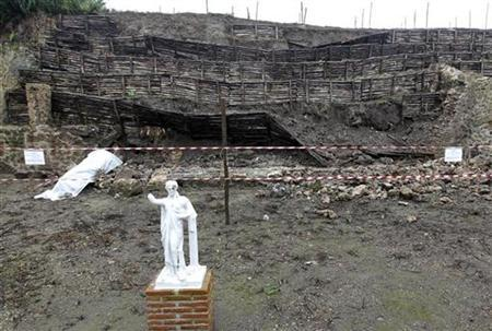 A statue is seen in front of a long section of a rustic retaining wall in the garden of the House of the Moralist, which collapsed after heavy rains in Pompeii November 30, 2010. REUTERS/Ciro De Luca