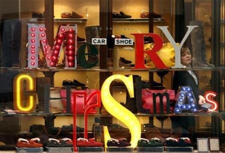 A shop assistant is seen behind the window of a shoe shop in downtown Rome December 21, 2009. REUTERS/Alessia Pierdomenico