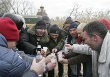 <p>Мужчины пьют водку из пластиковых стаканчиков в украинском селе Карловка 19 января 2008 года. За небольшую плату в украинском городе Днепропетровск теперь можно легко избавиться от одиночества и заказать себе на вечер собутыльника, пишет интернет-портал Сегодня.ua. REUTERS/Valeriy Bilokryl</p>