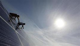 <p>Construction workers fix solar panels for a new solar power plant near Olching-Esting westward of Munich July 7, 2010. REUTERS/Michaela Rehle</p>