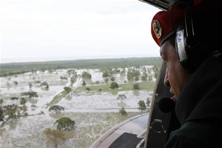 Venezuela's President Hugo Chavez watches through the door of a helicopter during a visit to the flooded areas on the south side of Maracaibo's lake in Maracaibo December 8, 2010. REUTERS/Miraflores Palace/Handout