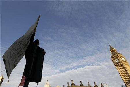 A demonstrator holds a banner during a protest in Westminster in central London December 9, 2010. REUTERS/Stefan Wermuth