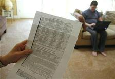 <p>Beth Stiner holds her appraisal summary for her rental home as her husband Aaron Stiner works on his computer at their rented home in Phoenix, Arizona December 11, 2010. The Stiner's were planning on buying their rental home, but they were unable to make the purchase based on the two different appraisals making the cost of the home too low for a lender to agree on a loan. A second home in Chandler, Arizona that the Stiner's own was appraised three times making it impossible for them to sell in the housing market. Picture taken December 11, 2010. REUTERS/Joshua Lott</p>