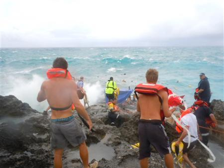 Rescuers are seen on the rocky shore on Christmas Island, where a refugee boat sank, in this handout December 15, 2010. REUTERS/ABC/Handout THIS IMAGE HAS BEEN SUPPLIED BY A THIRD PARTY. IT IS DISTRIBUTED, EXACTLY AS RECEIVED BY REUTERS, AS A SERVICE TO CLIENTS