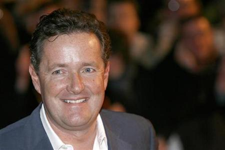 Piers Morgan poses for photographers as he arrives for the Brit Awards at Earls Court, in London February 18, 2009. REUTERS/Andrew Winning