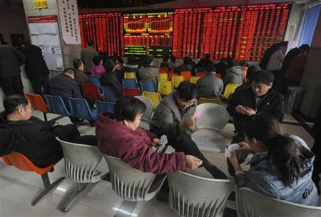 Investors play cards in front of an electronic board indicating rising stock prices, at a brokerage house in Taiyuan, Shanxi province December 13, 2010. REUTERS/Stringer