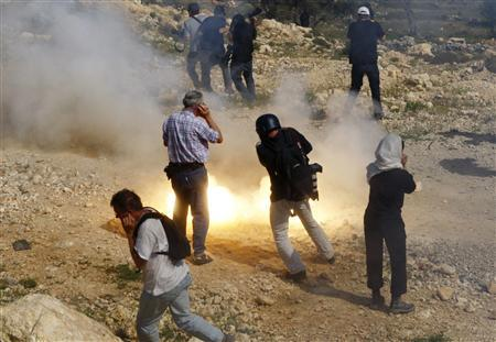 News photographers run from an exploding sound and light grenade thrown by Israeli troops during a violent protest against Israel's security fence in the West Bank village of Bilin in this March 28, 2008 file photograph. REUTERS/Yannis Behrakis/Files