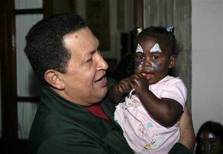 Venezuela's President Hugo Chavez carries a girl during a visit to a section of the Miraflores presidential palace which is housing displaced families due to recent torrential rains, in Caracas December 17, 2010. Venezuela's parliament gave Chavez the power to rule by decree for 18 months on Friday, outraging opponents who accused him of turning South America's biggest oil producer into a dictatorship. Chavez invited 25 families made homeless by torrential rains to stay temporarily at the palace in Caracas last month. REUTERS/Miraflores Palace/Handout THIS IMAGE HAS BEEN SUPPLIED BY A THIRD PARTY. IT IS DISTRIBUTED, EXACTLY AS RECEIVED BY REUTERS, AS A SERVICE TO CLIENTS