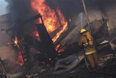 <p>Пожарный пытается потушить огонь, вызванный взрывом нефтепровда в городке Сан-Мартин-Тесмелукан, Мексика 19 декабря 2010 года. Взрыв на нефтепроводе в мексиканском городе в воскресенье унес жизни 28 человек, сообщили местные власти. REUTERS/Stringer</p>
