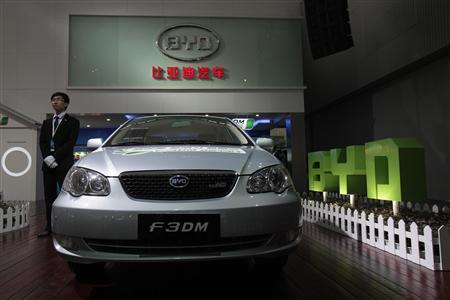An employee stands near a F3DM, a hybrid car by Chinese automaker BYD Auto, at the Guangzhou Autoshow December 20,2010. Chinese carmakers have been working to introduce their own designs to the country's auto market, which last year overtook the United States to become the world's biggest, fuelled by strong consumption and growing consumer affluence. REUTERS/Tyrone Siu