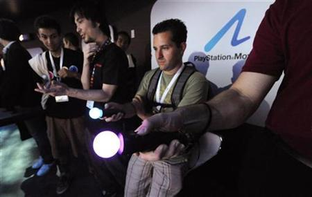 Attendees try out the PlayStation Move device for the Sony PlayStation 3 at the E3 Media & Business Summit in Los Angeles June 15, 2010. REUTERS/Phil McCarten