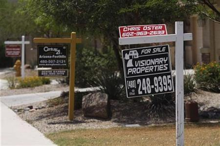Real estate signs are seen in the front yards of houses in this file photo taken in Maricopa, Arizona May 27, 2009. REUTERS/Joshua Lott/Files
