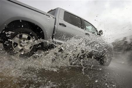 A truck drives through a flooded intersection in Los Angeles, California, December 21, 2010. REUTERS/David McNew