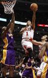 """<p>Игрок """"Чикаго"""" Деррик Роуз бросает мяч в корзина """"Лос-Анджелес Лейкерс"""" в Чикаго 10 декабря 2010 года. """"Чикаго"""" продолжил стремительный подъем в таблице Восточной конференции Национальной баскетбольной ассоциации, переиграв в ночь на четверг обескровленный травмами """"Вашингтон"""" 87-80. REUTERS/John Gress</p>"""