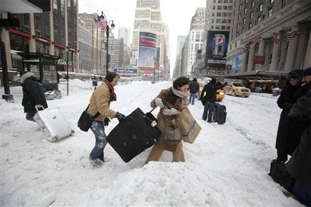 Travellers carry their luggage through a snow bank on 7th Avenue in front of Penn Station after a snow storm in New York December 27, 2010. REUTERS/Lucas Jackson