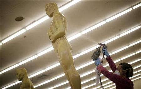 A woman spray paints Oscar statues in preparation for the 83rd Academy Awards in 2011, at Hollywood in Los Angeles, California, October 15, 2010. REUTERS/Lucy Nicholson