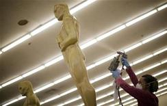 <p>A woman spray paints Oscar statues in preparation for the 83rd Academy Awards in 2011, at Hollywood in Los Angeles, California, October 15, 2010. REUTERS/Lucy Nicholson</p>