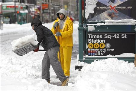 Workmen shovel snow from a sidewalk in Times Square in New York, December 27, 2010.REUTERS/Gary Hershorn