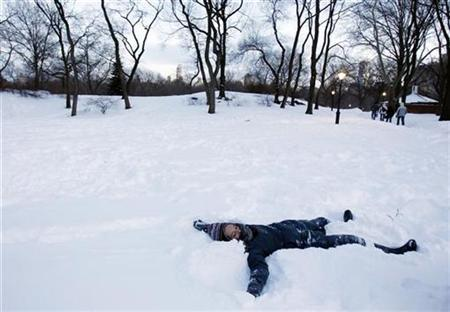 A girl makes a snow angel in New York's Central Park, December 27, 2010. REUTERS/Jessica Rinaldi