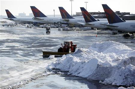 A plow clears snow on the tarmac at John F. Kennedy International Airport in New York, December 29, 2010. REUTERS/Jessica Rinaldi
