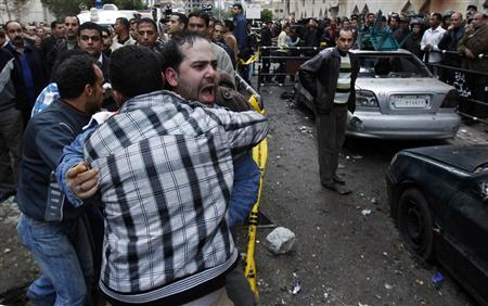 Egyptian Christians shout as the bodies (not in picture) of several victims of a car bomb attack are carried into ambulances in front of the the Coptic Orthodox church in Alexandria, 230 km (140 miles) north of Cairo January 1, 2011. REUTERS/Amr Abdallah Dalsh