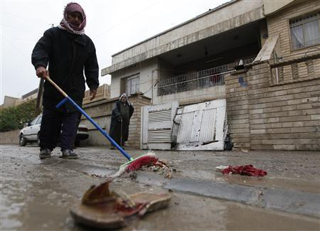 A resident cleans the site of a bomb attack that targeted Christians in Baghdad December 31, 2010. REUTERS/Mohammed Ameen