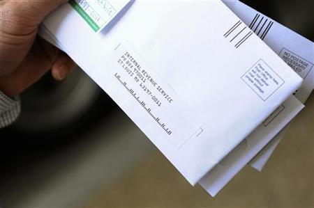 A man holds his envelopes as he waits in line to mail his family's income tax returns at a mobile post office near the Internal Revenue Service building in downtown Washington, April 15, 2010. REUTERS/Jonathan Ernst