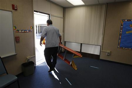 Maintenance worker Kent Burrows makes repairs at former Telechron Elementary School, which became the administrative offices of the South Whittier School District after budget problems forced the school to close this year, in Whittier, California, December 6, 2010. REUTERS/David McNew