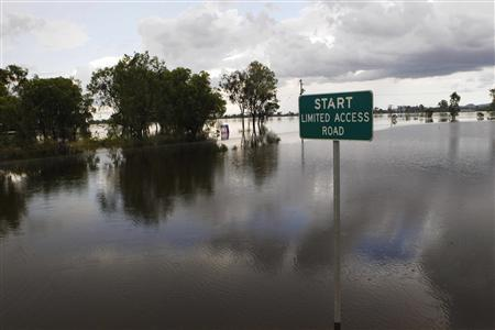 A street sign is seen partially covered by floodwaters 6km south of Rockhampton January 3, 2011. REUTERS/Daniel Munoz