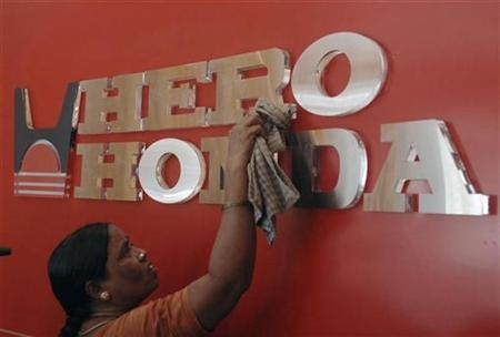 A worker cleans a Hero Honda logo inside its showroom in the southern Indian city of Hyderabad April 19, 2010. REUTERS/Krishnendu Halder
