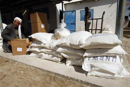 A Palestinian man sits next to sacks of flour received from the United Nations Relief and Works Agency (UNRWA) headquarters in Khan Younis in the southern Gaza Strip November 9, 2010. REUTERS/Ibraheem Abu Mustafa