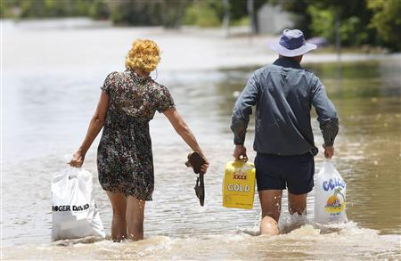 A couple carry supplies as they walk through floodwaters in Depot Hill in Rockhampton, Queensland, January 5, 2011. REUTERS/Daniel Munoz