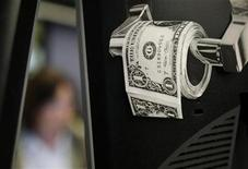 <p>A magazine cut-out of a toilet roll made up of paper money, is taped to a screen of a trading terminal at the German stock exchange in Frankfurt, June 3, 2009. REUTERS/Kai Pfaffenbach</p>