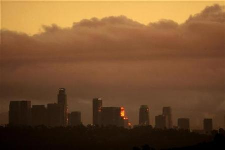 Storm clouds are seen from the La Canada Flintridge area as the setting sun is reflected in buildings in downtown Los Angeles, California December 22, 2010. REUTERS/David McNew