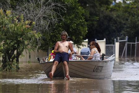 A man sits in the front of his boat as he navigates through floodwaters in Depot Hill in Rockhampton, Queensland, January 5, 2011. REUTERS/Daniel Munoz