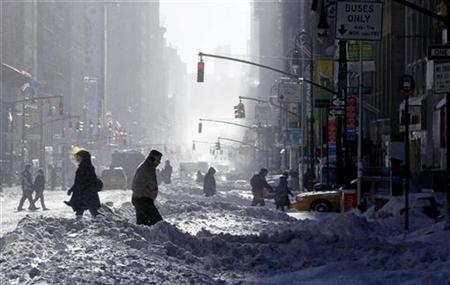 People walk through the snow on 7th Avenue in New York, December 27, 2010. REUTERS/Gary Hershorn