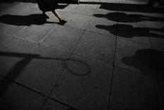 <p>Shadows are seen as a woman walks down Bay Street in the financial district</p>
