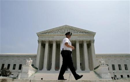 A Supreme Court police officer patrols outside the Supreme Court building in Washington, July 1, 2005. REUTERS/Shaun Heasley